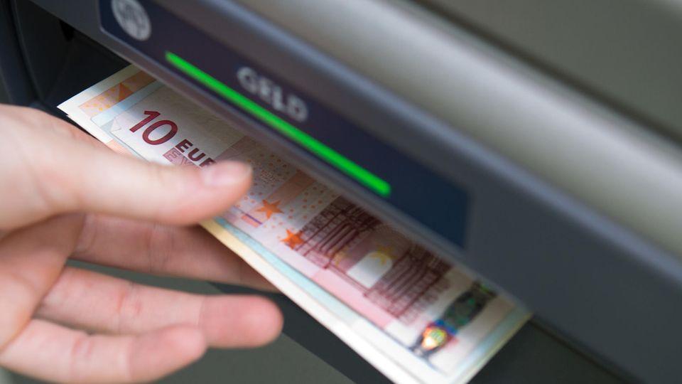 Eine Hand greift nach Geldscheinen, die aus einem Geldautomaten ausgeworfen wurden