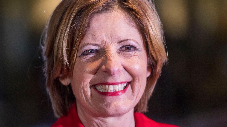 Une femme aux cheveux auburn et au blazer rouge sourit largement en fronçant le nez.