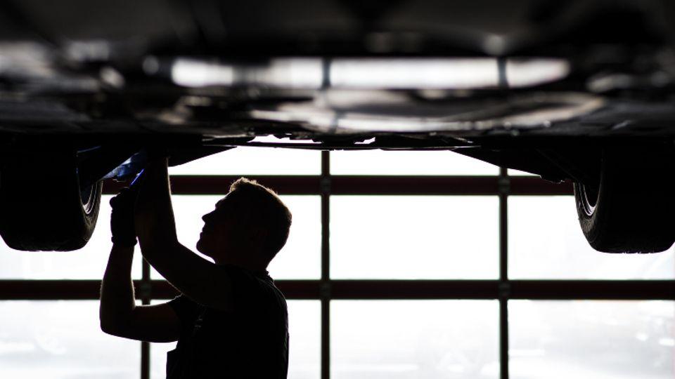 Mechaniker arbeitet in einer KfZ-Werkstatt an der Unterseite eines Autos.