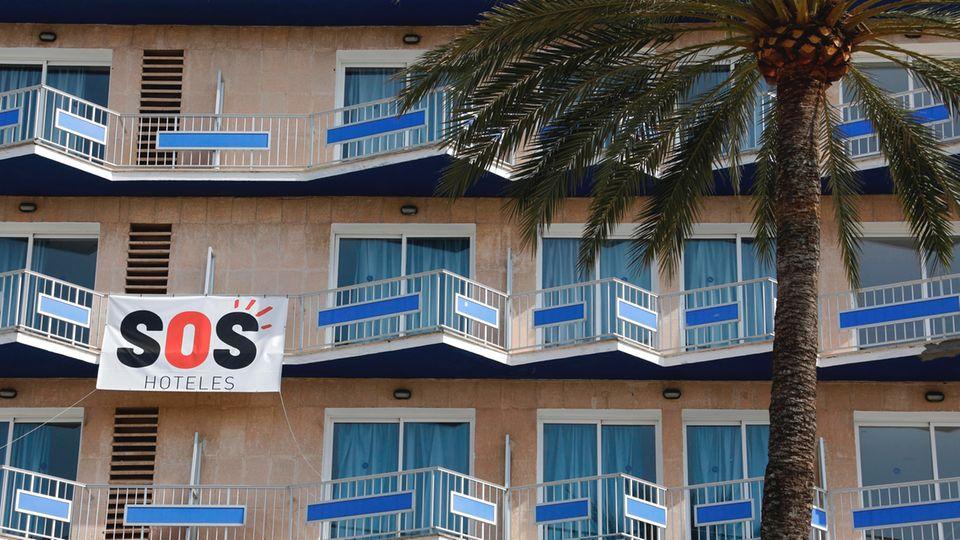 """Ein Transparent mit der Aufschrift """"SOS Hoteles"""" hängt an der Fassade eines Hotels auf Mallorca."""