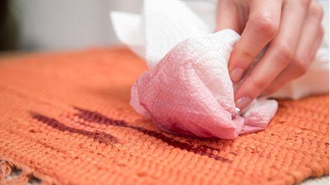 Frau tupft Rotweinfleck mithilfe eines Küchenpapiers aus einem Teppich.