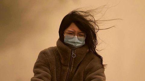 Eine junge Chinesin mit langen schwarzen Haaren fährt mit OP-Maske durch den Sandsturm, der den Himmel gelb einfärbt