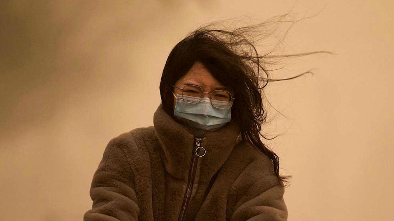 Une jeune femme chinoise aux longs cheveux noirs traverse la tempête de sable en portant un masque chirurgical, ce qui rend le ciel jaune.