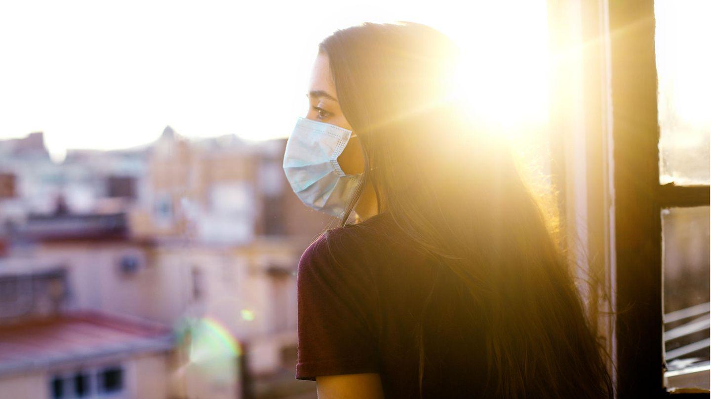Frau mit Maske am Fenster im Sonnenschein