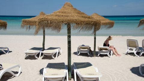 Eine Urlauberin sitzt am Strand an der Platja de Muro auf Mallorca