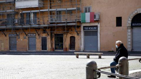 Ein Mann sitzt auf dem fast menschenleeren Navona-Platz in Rom