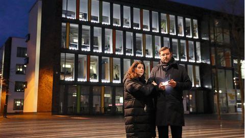 Tim Kurzbach (SPD) mit seiner Frau vor dem Rathaus. In Kurzbachs Hand und in den Fenstern leuchten Lichter zum Gedenken an die Corona-Toten