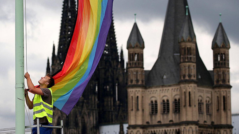 Ein Arbeiter hängt vor der Kulisse des Kölner Doms und der Kirche Groß St. Martin eine Regenbogenfahne auf