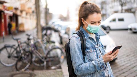 Frau mit Alltagsmaske steht an einer Straße und schaut auf ihr Handy
