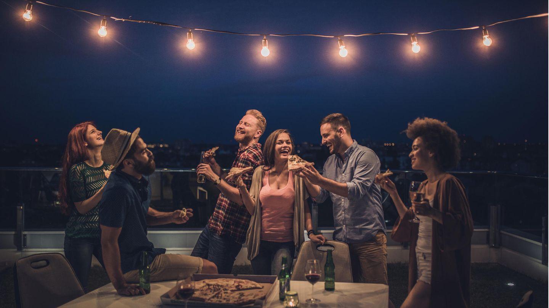 Balkonbeleuchtung: Eine Gruppe junger Menschen feiert in der Nacht auf dem Balkon unter einer Lichterkette