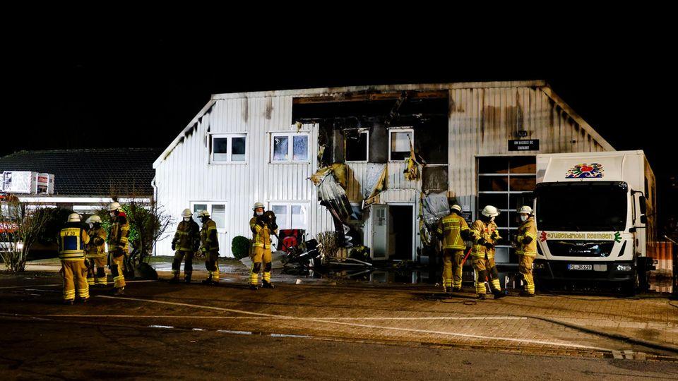 Einsatzkräfte der Feuerwehr stehen vor dem Gebäude einer Caravan-Ausbaufirma