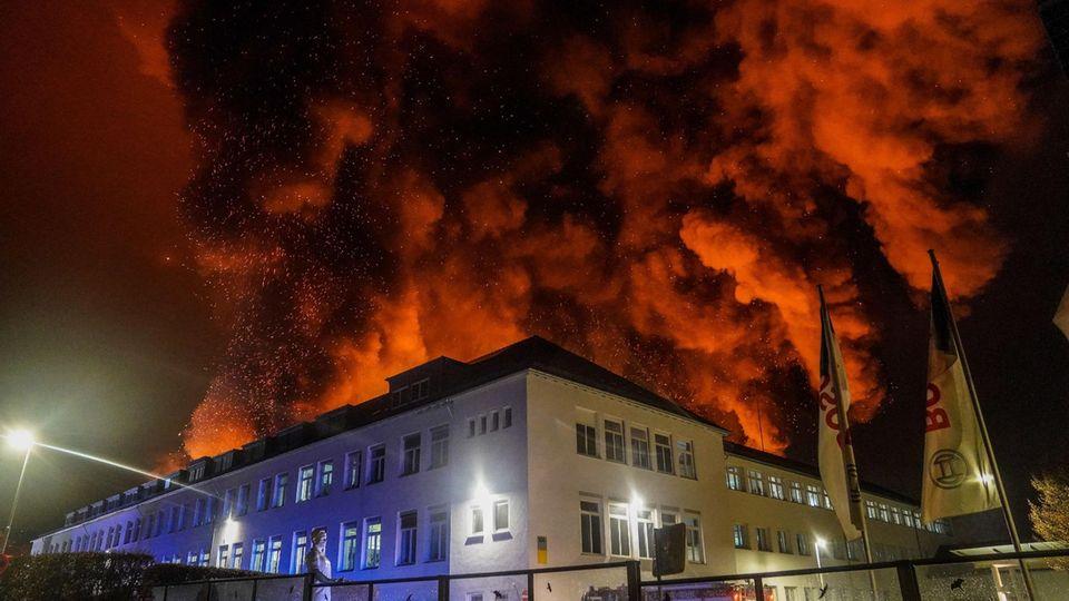 Eine starke Rauchwolke steigt bei einem Großbrand über einem Firmengelände auf
