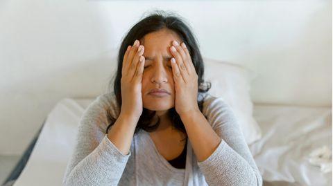 Eine Frau hält sich ihre Hände an die Schläfen und Wangen