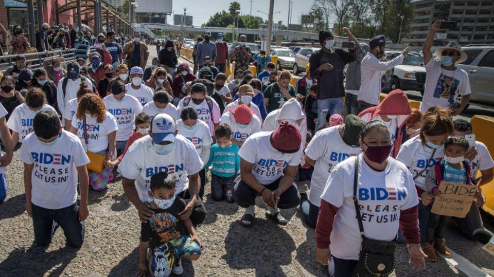 """Eine Gruppe Migranten kniet am US-Grenzübergang und betet. Auf ihren T-Shirts steht: """"Biden, lass uns bitte rein"""""""