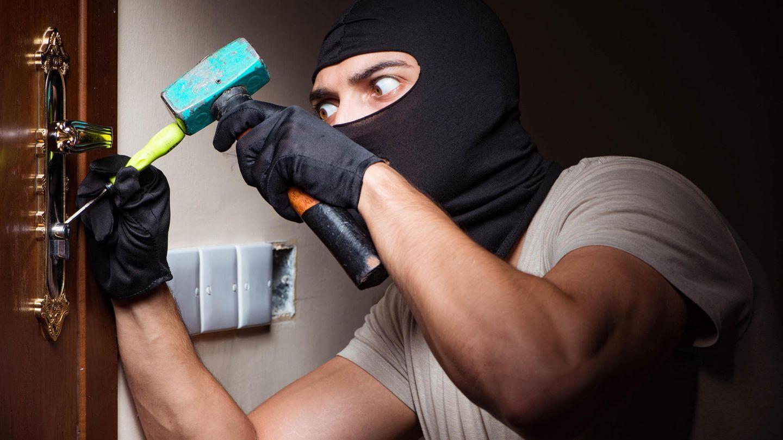 Ein junger Mann mit Sturmhaube versucht, ein Türschloss aufzuschrauben