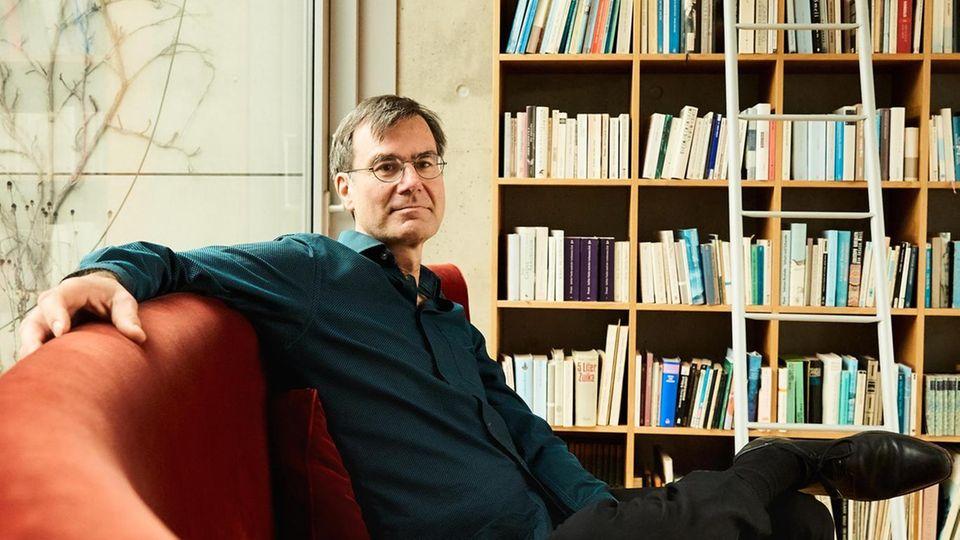 Stefan Klein vor seiner Bücherwand