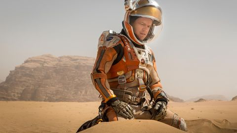 Astroanut Mark Watney alias Matt Damon kniet im Marssand