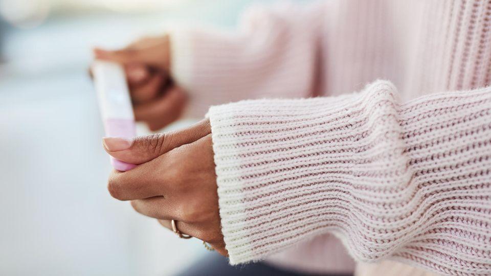 Eine Frau mit rosa Pulli hält einen Schwangerschaftstest