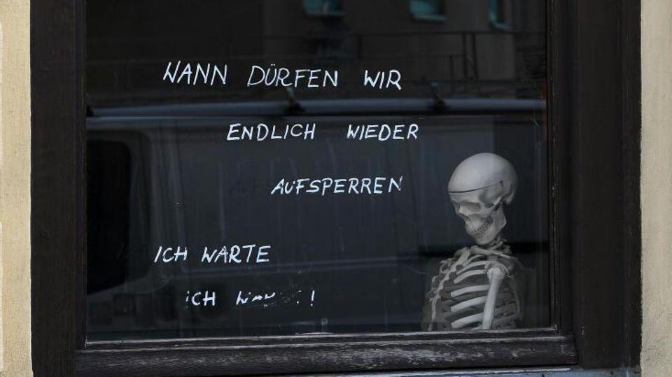 Ein Skelett sitzt in einem Café am Fenster