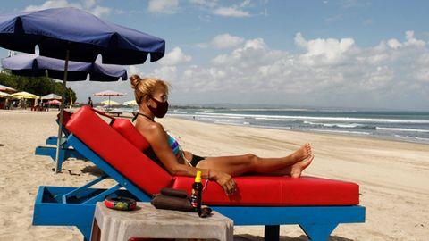 Eine Frau sonnt sich im Bikini auf einer blauen Strandliege mit dicker roter Auflage