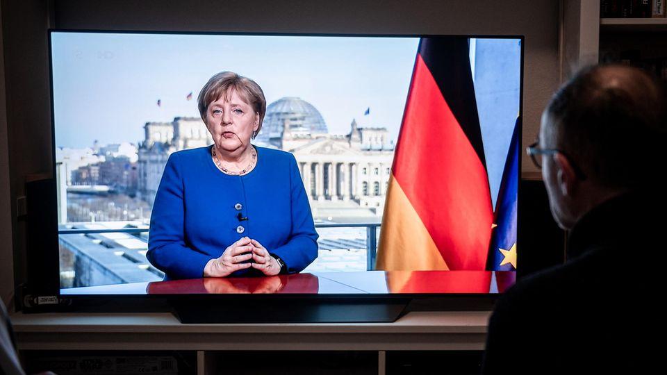 Menschen schauen am 18. März 2020 die TV-Ansprache von Bundeskanzlerin Angela Merkel (CDU)