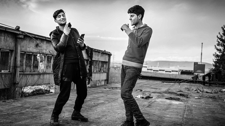 """""""Diese beiden Männer sind Cousins. Der Linke heißt Zeeshan Akash Khan und ist auf dem Bild 20 Jahre alt, der Rechte ist Ikham Khan, 17 Jahre alt. Sie kommen aus Pakistan. Sie stehen hier auf demselben Vordach, auf dem ich die Männer auf dem vorhergehenden Bild beim Kochen fotografiert hatte. Diese beiden nutzten diesen Ort um sich ein bisschen zu vergnügen. Zeeshan spielte Hochzeitsmusik auf dem Handy und sie tanzten dazu.  Während der Zeit, die ich in Bihac verbrachte, begegnete ich Zeeshan und Ikham mehrmals. Und wann immer ich sie traf, waren sie guter Laune. Das war auffällig und es hat mich beeindruckt. Irgendwann habe ich sie gefragt: """"Warum seid Ihr so gut drauf? Eure Lage ist ja nicht gerade rosig."""" Da hat Zeeshan geantwortet: """"Was soll ich denn sonst tun? Ich mag nicht immer schlechte Laune haben.""""  Bei diesem Bild geht es mir darum zu zeigen, wie diese Menschen versuchen, ihre Würde zu wahren. Nicht zu vergessen, wie sie sich selbst sehen – ungeachtet der Umstände, in denen sie gerade leben. Natürlich wissen Zeeshan, Ikham und all die anderen Flüchtenden, wie schlecht ihre Lage ist. Trotzdem achten diese beiden auf ihren Style. Einen von ihnen hatte ich kurz vorher getroffen, als er sich gerade die Haare schneiden ließ. Die beiden lassen sich nicht auf die Umgebung reduzieren, in der sie dort gerade stecken. Aus diesem Bild spricht für mich ein unbedingter Durchhaltewillen. Es sagt: 'Seht her, wir sind mehr als das, was die Flucht aus uns macht.'"""""""