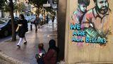 """Beirut, Libanon.EineFrau sitzt mit ihrer Tochter auf dem Boden und bettelt. Auf der Wand hinterihr prangt ein Graffitomit dem Satz: """"Wir sind alle Bettler""""."""