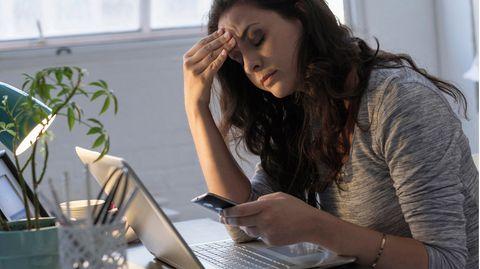 Geschäftsfrau schaut frustriert auf Smartphone und Laptop