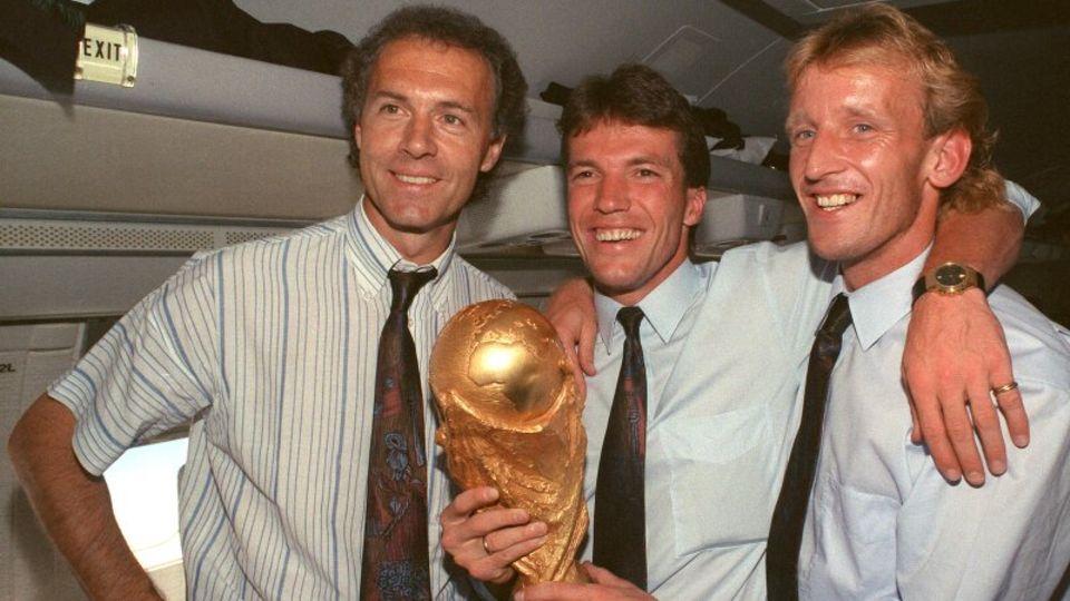 Franz Beckenbauer, Lothar Matthäus und Andreas Brehme posieren mit Weltmeisterschaftspokal.
