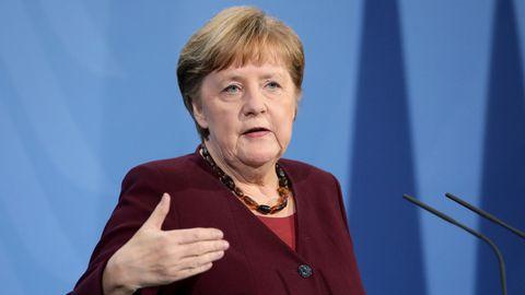 Angela Merkel steht in weinrotem Blazer vor einer blauen Wand, spricht in zwei Mikros und gestikuliert mit rechts