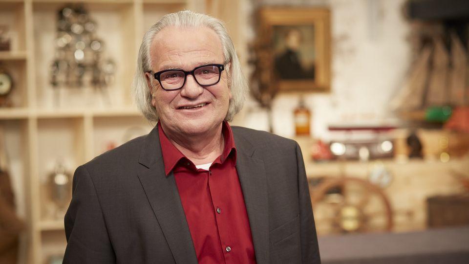 Albert Maier steht im Bares für Rares Studio in Pulheim und lächelt in die Kamera
