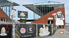 """Die Graffiti an den Wänden des Millerntors heben es optisch von den anderen Fußballstadien ab. Im Bild rechts ist mit der Spielanzeige in der Hand die Figur des Künstlers """"Rebelzer""""zu sehen."""