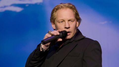 Ben Becker steht bei einer Lesung auf der Bühne und hält das Mikrofon