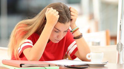 Studentin beugt sich über ihre Notizen