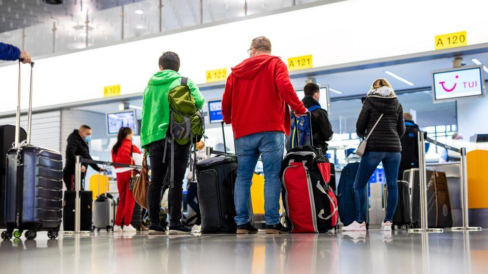 Fluggäste mit dem Reiseziel Mallorca stehen im Flughafen Hannover-Langenhagen am Check-in