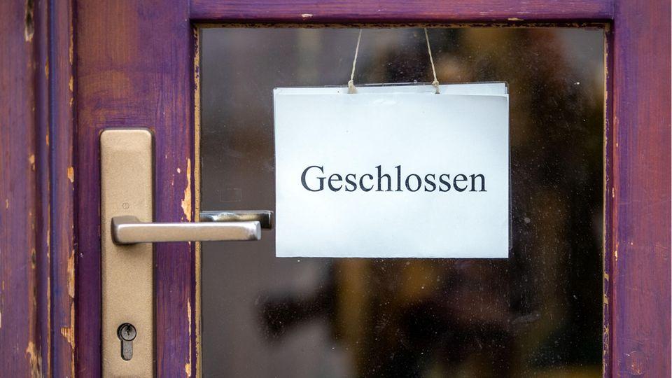 """Ein Schild mit der Aufschrift """"Geschlossen"""" hängt während der Corona-Pandemide an der Tür eines Ladengeschäfts"""