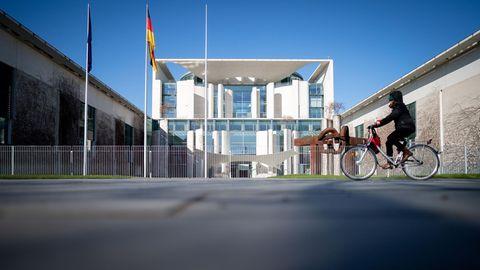 Eine Radfahrerin fährt am Morgen am Bundeskanzleramt vorbei