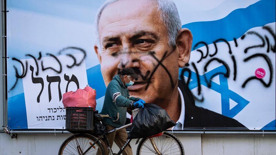 Ein Mann schiebt ein Fahrrad an einem beschmierten Wahlkampfplakat der Likud-Partei vorbei