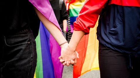 Ein homosexuelles Paar hält Hände vor einer Regenbogenflagge.