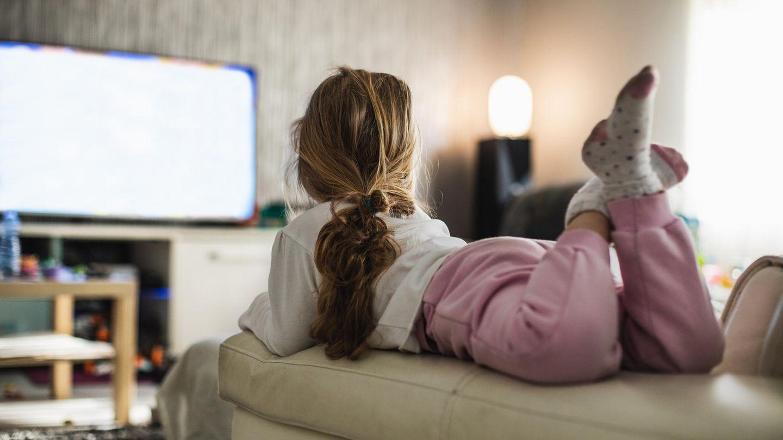 Mädchen liegt auf einer Couch und schaut Fernsehen