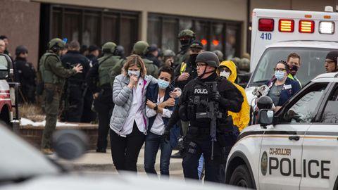 Menschen werden vom Tatort in Boulder, Colorado weggebracht