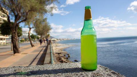 Ein Flasche Bier steht an einem Gewässer
