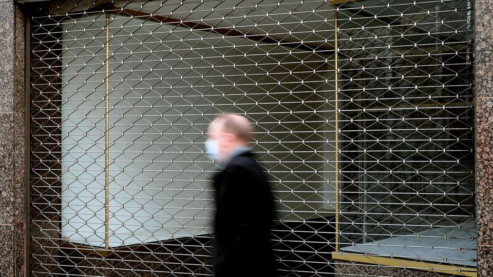 Mann mit Mundschutz geht an einem geschlossenen Geschäft vorbei.