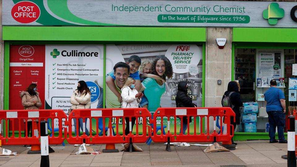 Menschen stehen vor einer Londoner Apotheke Schlange