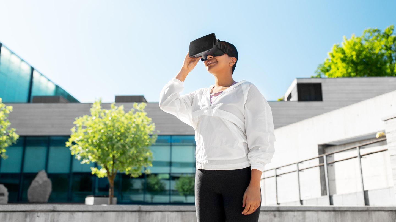 Eine Person trägt eine Virtual Reality-Brille und steht vor einem Haus