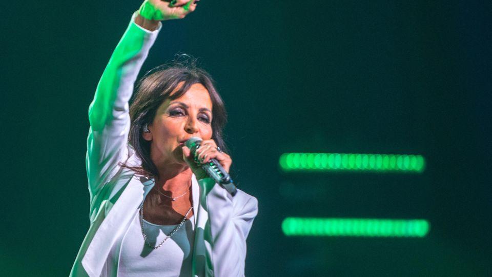 Nena streckt bei einem Konzert in der Frankfurter Festhalle 2019 den Arm nach oben