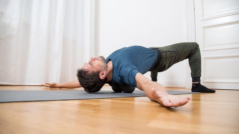 Triggerpunktmassage: Mann liegt mit zwei Massagebällen im Rücken auf eine Gymnastikmatte