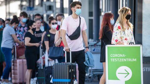 Reiserückkehrer aus Spanienstehen mit Mundschutz vor dem Corona-Testzentrum am Flughafen Stuttgart an