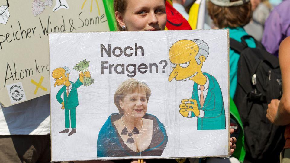 Eine Demonstrantin hält in Gronau ein Transparent gegen Atomkraft mit Merkel und Mister Burns drauf in der Hand.
