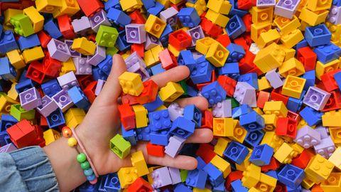 Hand greift in große Menge Legosteine